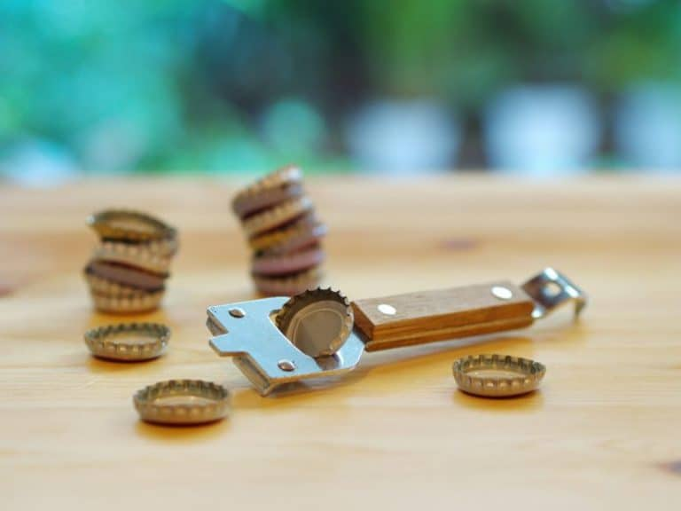 a bottle opener with bottle caps scattered around