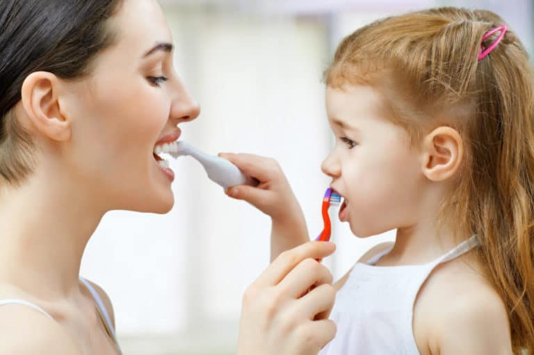 mother and daughter brushing each other's teeth