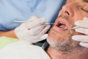 man under conscious sedation during dental cleaning